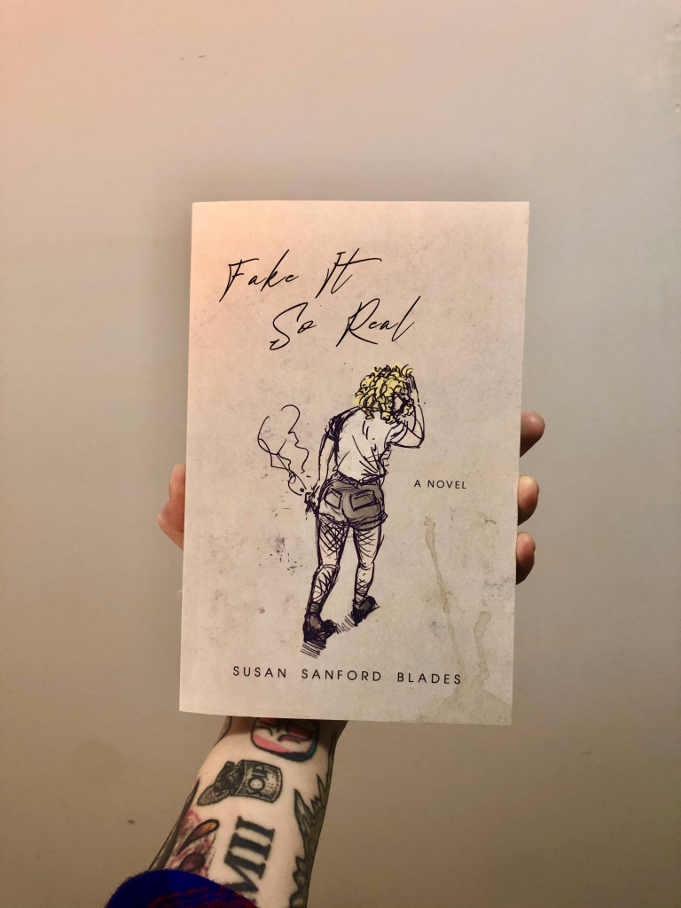 susan sand ford blade's book fake it so real being held by an arm